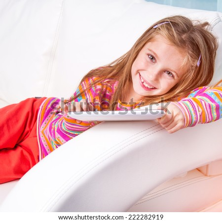 happy cute little girl with the tablet  at home - stock photo