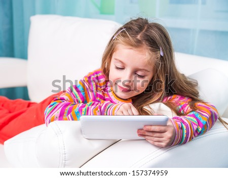 happy cute little girl with the tablet on a white sofa