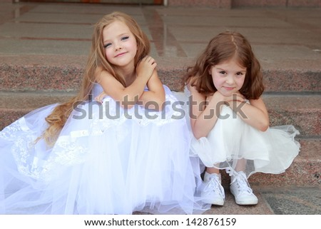 Happy cute little girls with long hair in long white dresses sitting on the steps