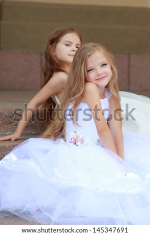 Happy cute little girls with long hair in long white dresses sitting on the steps - stock photo