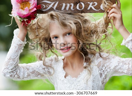 Happy cute little girls with long hair in white dresses sitting on the grass with wooden plaque with text about love portrait little bridesmaid  with bouquets  Teenage Girl Having Fun in Autumn Park  - stock photo