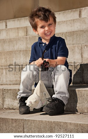Happy cute little smiling boy sitting on stairs - stock photo