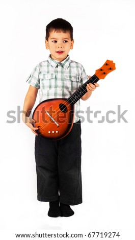 Happy  cute little thoughtful boy playing guitar, playing with toys.