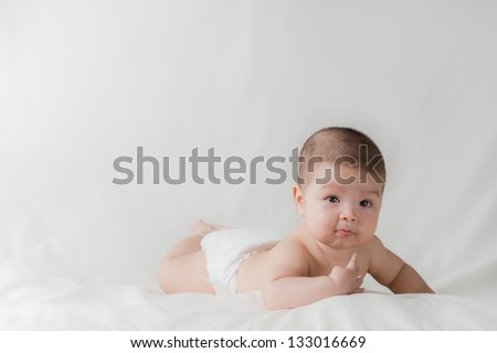 Happy cute 5 month old Asian baby boy with short black hair wearing a white cloth nappy and lying on his front on a white bed - stock photo