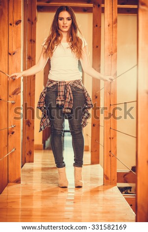 Happy cute pretty gorgeous woman at home. Attractive young girl with long hair wearing white shirt, jeans trousers and high heels. Instagram filter. - stock photo