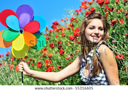 happy cute teen girl having fun with windmill on the poppy field - stock photo