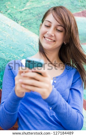happy cute teenage girl text messaging smiling with joy. vertical shot - stock photo