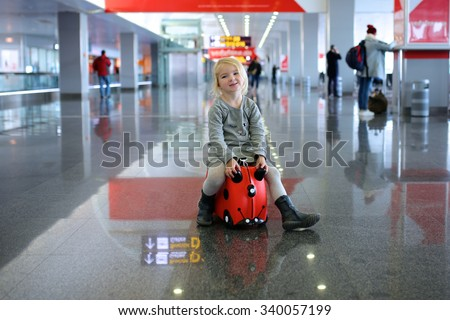 Happy cute three years old girl riding on suitcase in the airport. Family with kids going on vacation. - stock photo