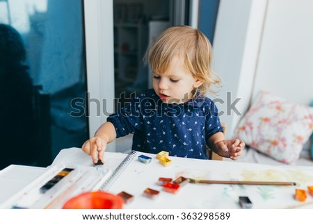 Happy cute toddler girl painting with gouache and watercolor paints on the balcony  - stock photo