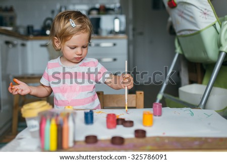 Happy cute toddler painting with gouache paints in the kitchen - stock photo