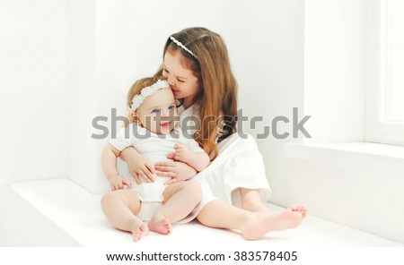 Happy cute two sisters children playing together at home in white room