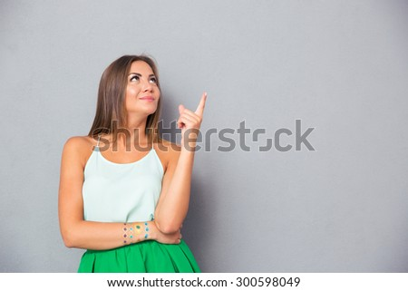 Happy cute woman pointing finger up at copyspace over gray background - stock photo