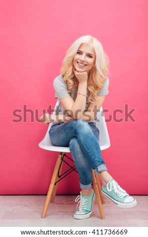 Happy cute woman sitting on the chair over pink background