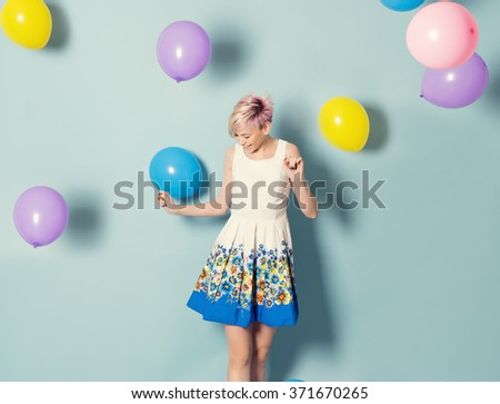 happy cute woman with balloons in studio - stock photo