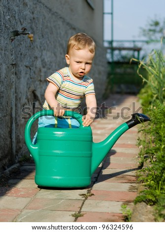 Happy cute young boy playing with the watering can in the garden