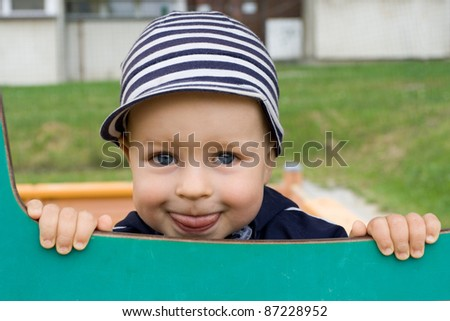 Happy cute young boy smiling on the playground - stock photo