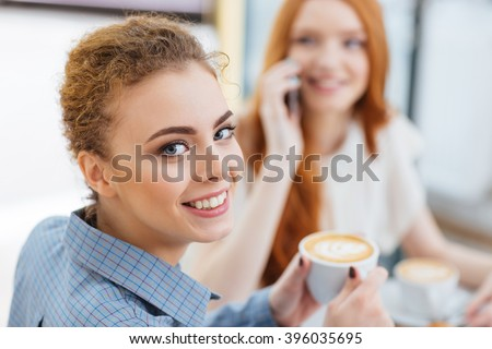 Happy cute young woman drinking coffee with her friend in cafe  - stock photo