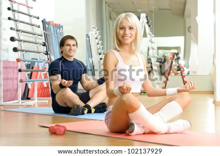 happy cutie athletic girl and guy,  execute exercise  and smile, in  sport-hall - stock photo