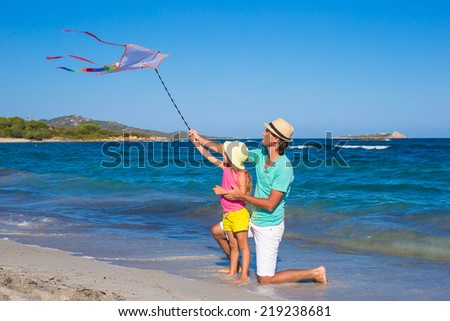 Happy dad and cute little daughter flying kite together - stock photo