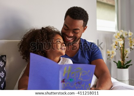 Happy dad and daughter in bed with card on birthday morning - stock photo