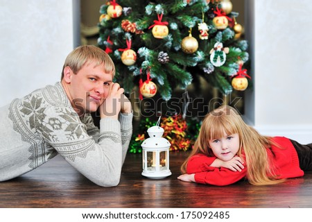happy dad and daughter lies on the floor near the Christmas tree - stock photo
