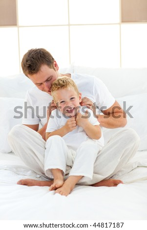 Happy dad and his son playing together on a bed - stock photo