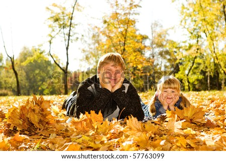 Happy dad and preschool daughter lying on the autumn leaves