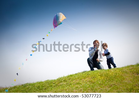 happy dad and son flying a kite together - stock photo