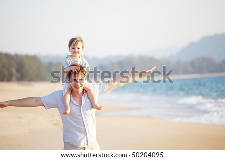happy dad and son having fun on the beach - stock photo