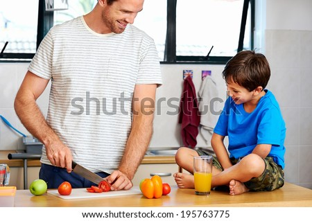 happy dad and son making healthy food together in kitchen - stock photo