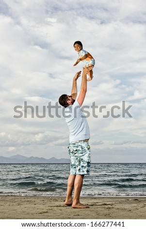 happy dad at the beach playing with his baby