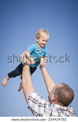 Happy dad holding young son up against blue sky - stock photo