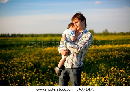 happy dad keeping his tired son in his arms in the field of dandelions - stock photo