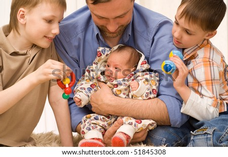 happy dad plays with his three children