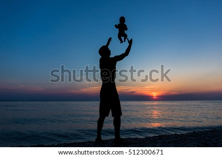 Happy dad throws toddler at sunset background