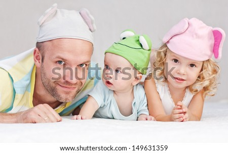 happy dad with kids in funny hats lying on the bed - stock photo