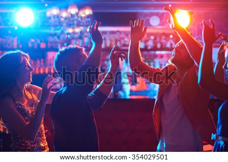 Happy dancers enjoying disco in night club - stock photo