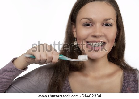happy dark hair girl meets new day with toothbrush having her mouth open with braces on teeth smiling with positive expression isolated over white background - stock photo