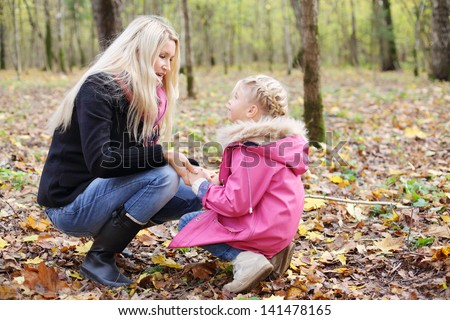 Happy daughter and mother hunker down and look at each other in autumn forest. Focus on mother. Shallow depth of field.