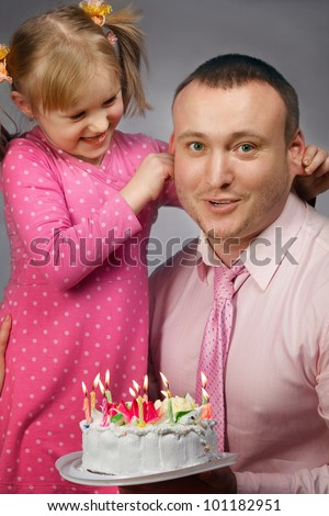 Happy daughter pulling on her father's ears in his birthday - stock photo