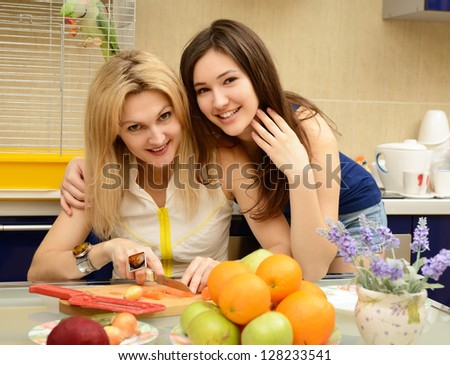 Happy daughter teenager with her mother peel and cut vegetables together in kitchen at home - stock photo