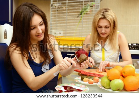 Happy daughter teenager with her mother peel and cut vegetables together in kitchen at home