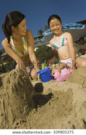 Happy daughter with mother making sand castle on beach - stock photo