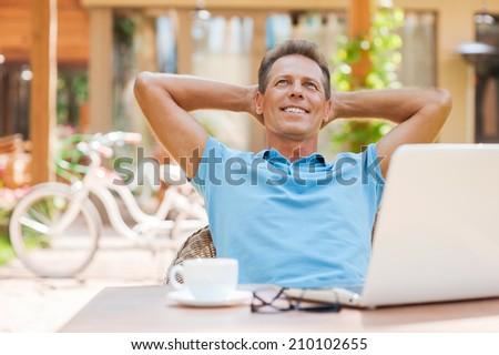 Happy day dreamer. Relaxed mature man holding hands behind head and smiling while sitting at the table outdoors with laptop on it  - stock photo