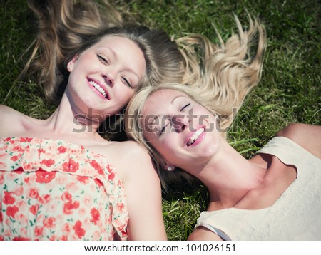 happy day in nature. two girls lay on a field - stock photo