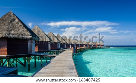 Happy days in Maldives, islands with vivid clear sea water, pretty endless beach, soft white sands,  luxury water villa, straight coconut trees, wonderful sunset and sun rise, blue sky with clouds. - stock photo