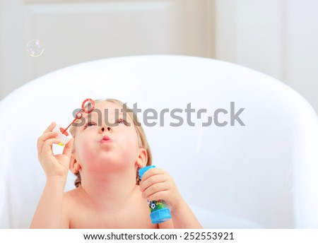 Happy days of childhood. Cropped image of a cute little girl taking a bath and playing with soap bubbles while sitting in a luxurious bathtub  - stock photo