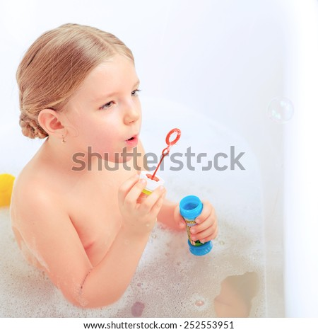Happy days of childhood. Top view image of a cute little girl taking a bath and playing with soap bubbles while sitting in a luxurious bathtub