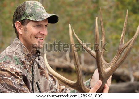 happy deer hunter holding antlers - stock photo