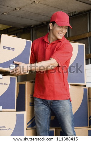 Happy delivery man arranging cardboard boxes